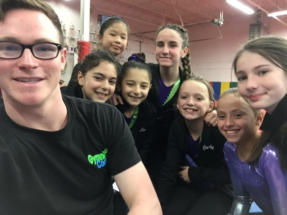 Gymnastics coach with gymnasts at gymnastics competition